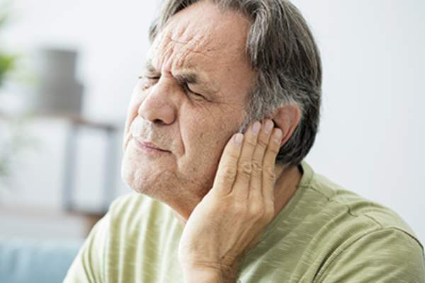Man with ear pain holding his ear.