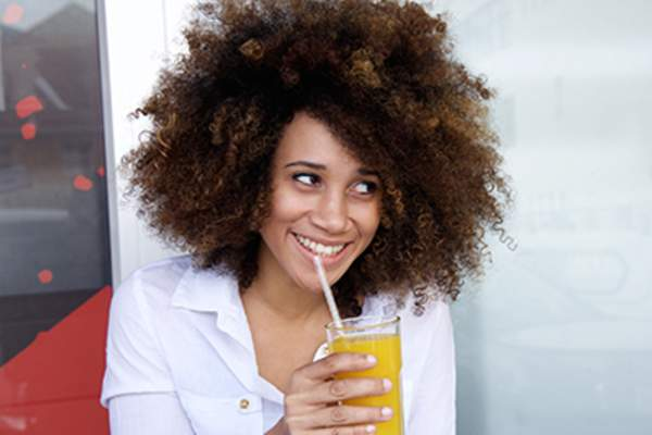 Smiling woman drinking juice through a straw.