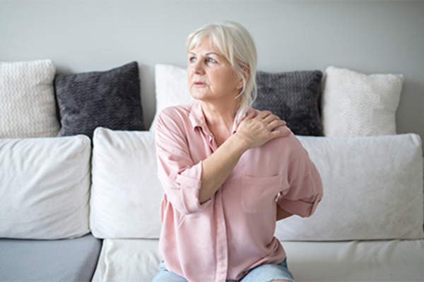 Woman in pain sitting on couch at home.