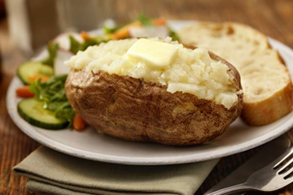 Baked potato with vegetables and bread.