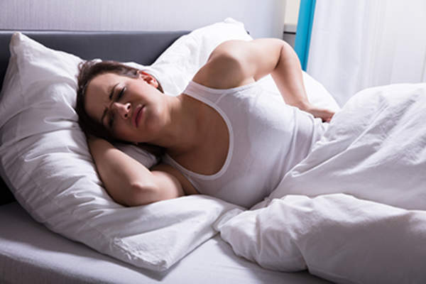 Woman struggling to sleep with back pain.