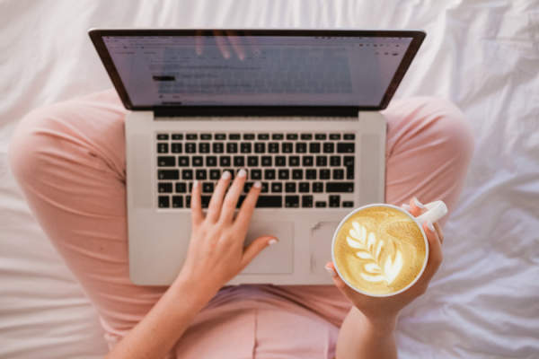 woman on bed with laptop holding latte