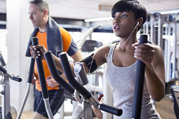 Young woman and man working out on ellipticals at the gym.