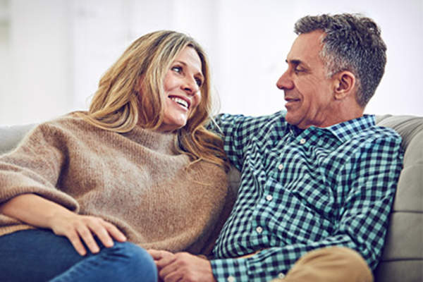 Mature couple having a conversation at home on couch.