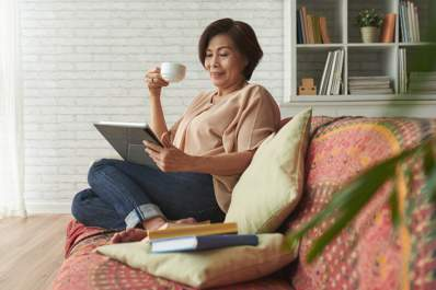 Woman drinking tea and reading on couch at home.