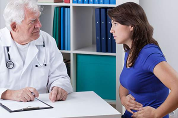 Woman discussing stomach problems with her doctor.