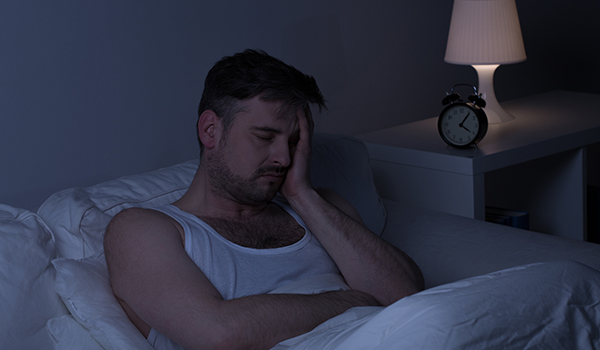 Man sitting in bed at night with a headache.