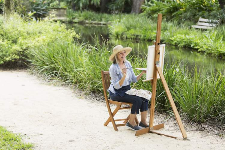 Older woman painting on canvas by stream.