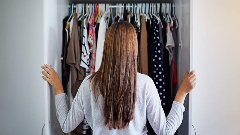 Young woman with long hair looking in her closet.