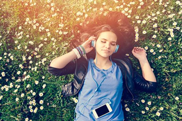 Woman in the park relaxing in the grass and listening through headphones.