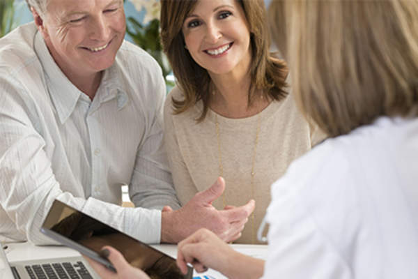 Doctor using tablet and smiling adult couple.