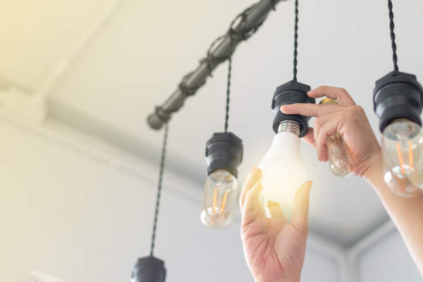 close up of man's hands changing lightbulbs to energy efficient ones