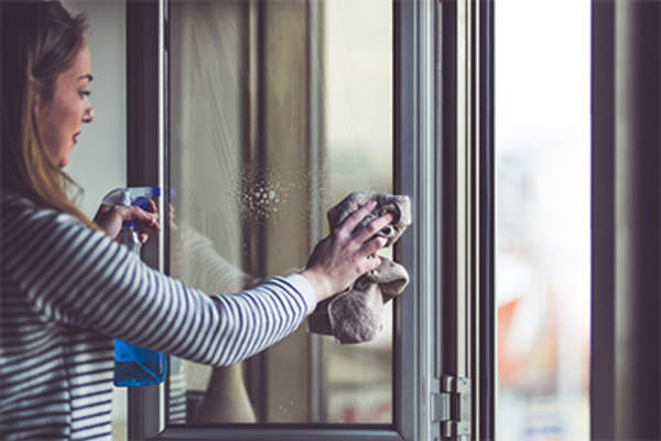 Woman washing window at home.
