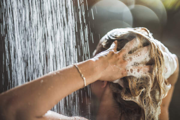 Woman washing her hair with shampoo in the shower.