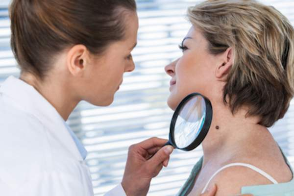 Dermatologist examining mole with magnifying glass