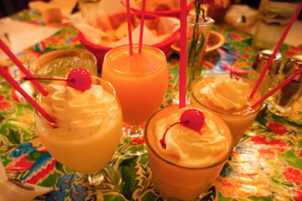 Four fruit based cocktails on party table.