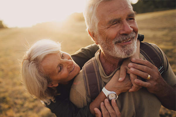 Senior couple smiling and embracing outside in sunshine.