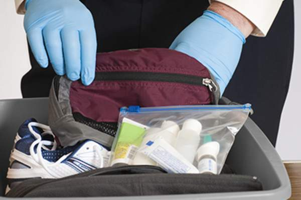 TSA agent checking carry on luggage with medicine in it.
