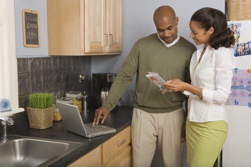 Couple in kitchen looking at travel brochure