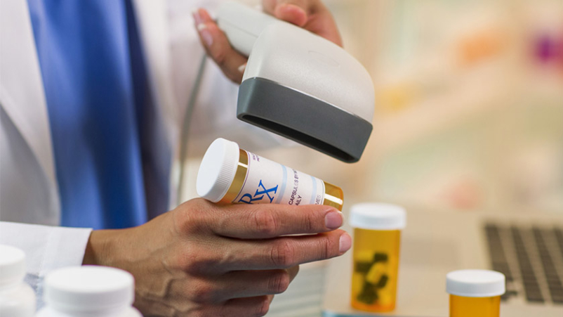 Pharmacist scanning prescription medication.