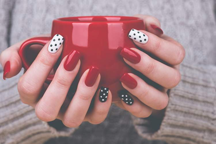 Manicured hands with polka-dotted nail polish holding a coffee cup.