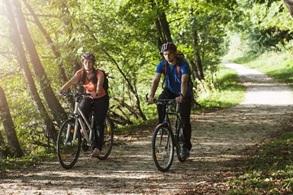 Couple biking on trail in the summer.
