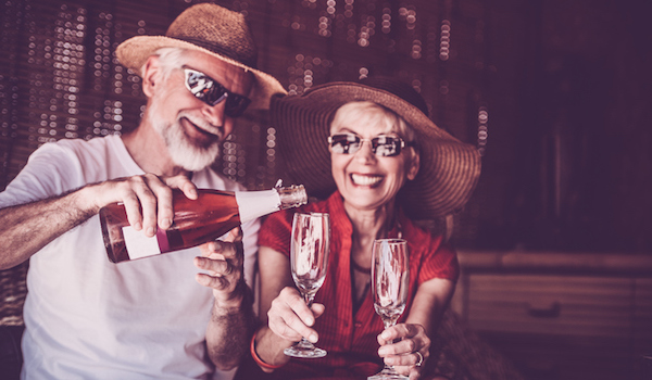 Older couple enjoying vacation by pouring sparkling wine.