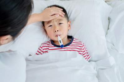 Sick child has his temperature taken by his mother.