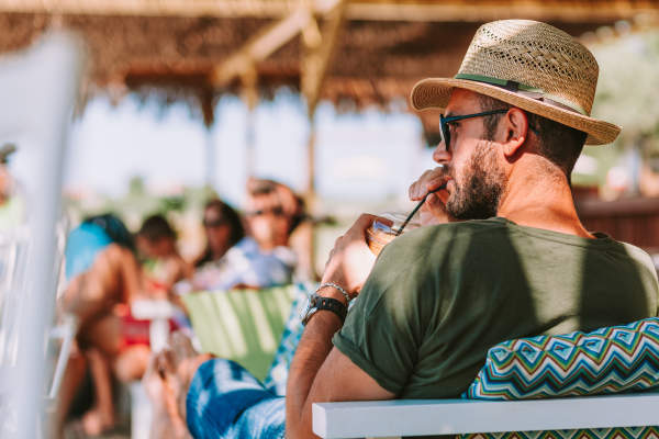 Man in cotton shirt and straw hat, drinking beverage, on vacation