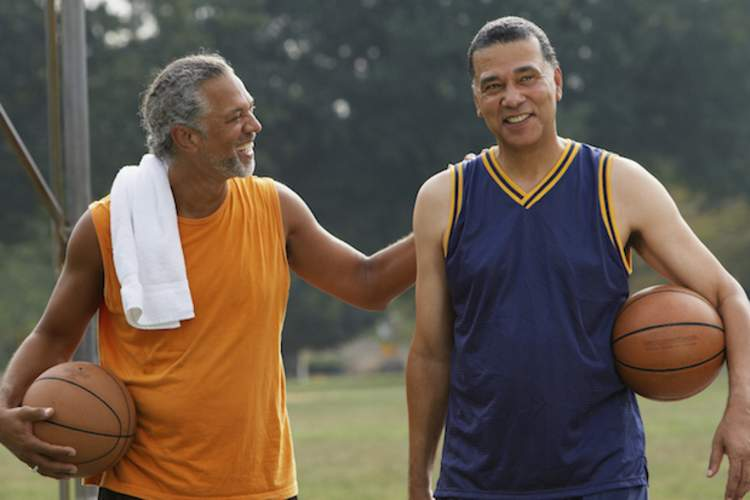 Two men talk to each other on the basketball court.