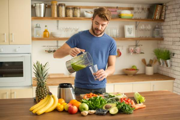 Young man making juice or smoothie in kitchen