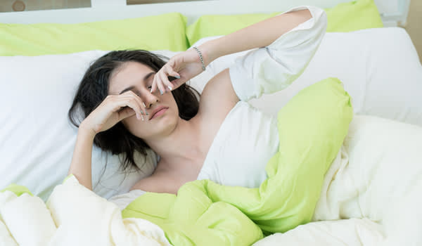 Young woman rubbing eyes in bed.