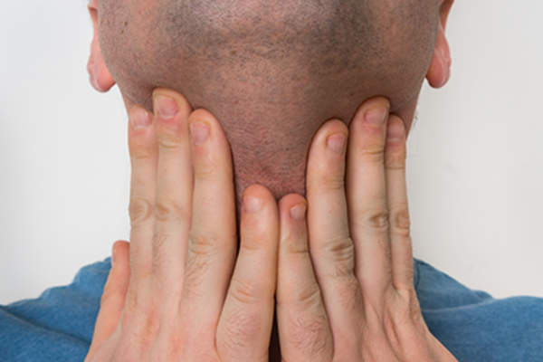 Man with hands on the front of his neck, thyroid, throat.
