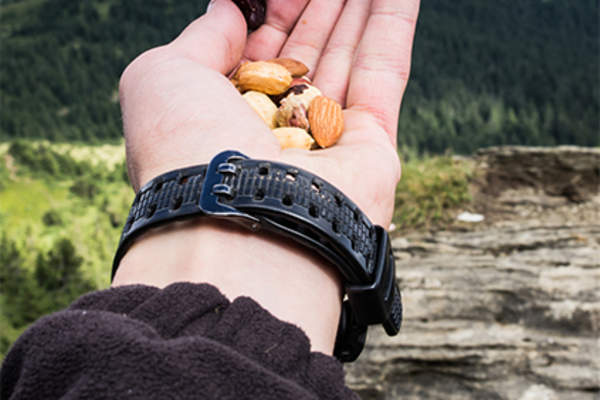 Man holding a handful of mixed nuts while hiking.