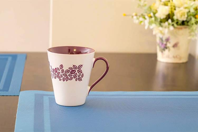 Flowered coffee cup on table.