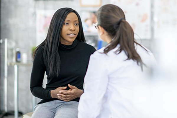 Woman discussing ulcerative colitis with her doctor.