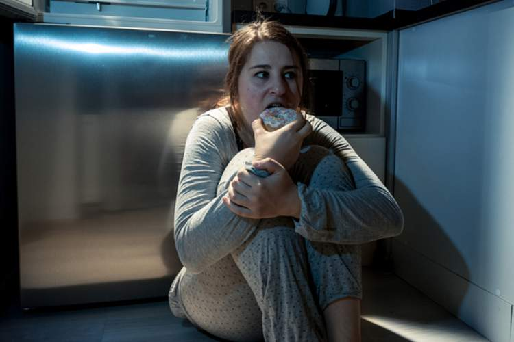 Woman sitting on kitchen floor eating at night.