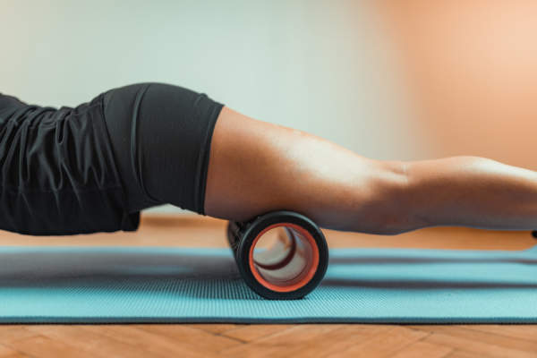 close up of woman's legs using foam roller
