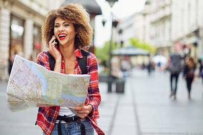 Woman wandering through a foreign city with a map.