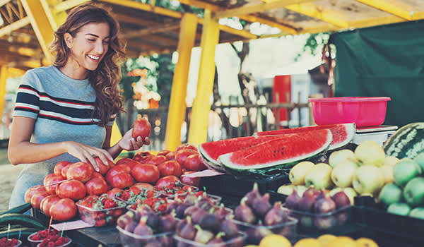 Woman buying fruits at a farmer's market.
