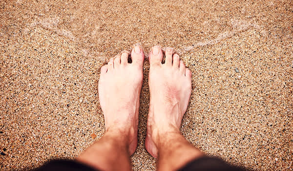 Man standing with his feet together in the sand near the ocean.