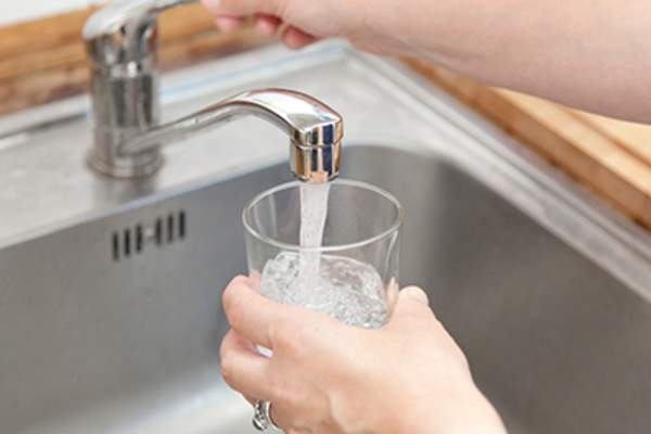 Woman filling a glass with tap water.