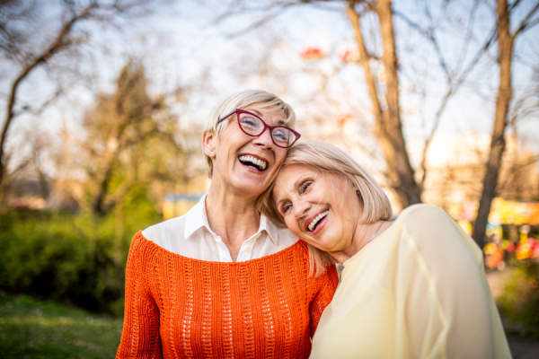 Two senior women laughing at the park