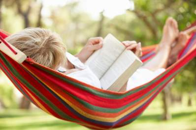 Senior woman relaxing in a hammock while reading a book.