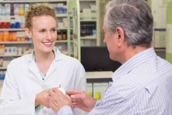 Pharmacist helping older male patient.