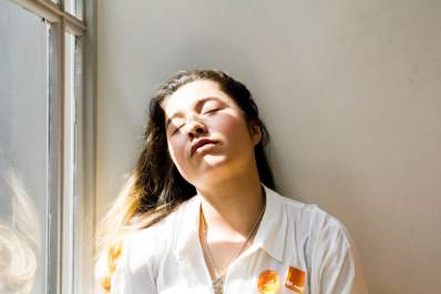 young tired woman with eyes closed in sunlight