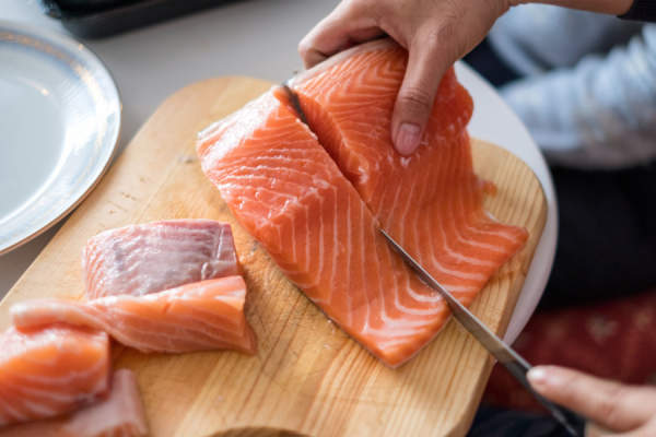 Woman's hands cutting raw salmon