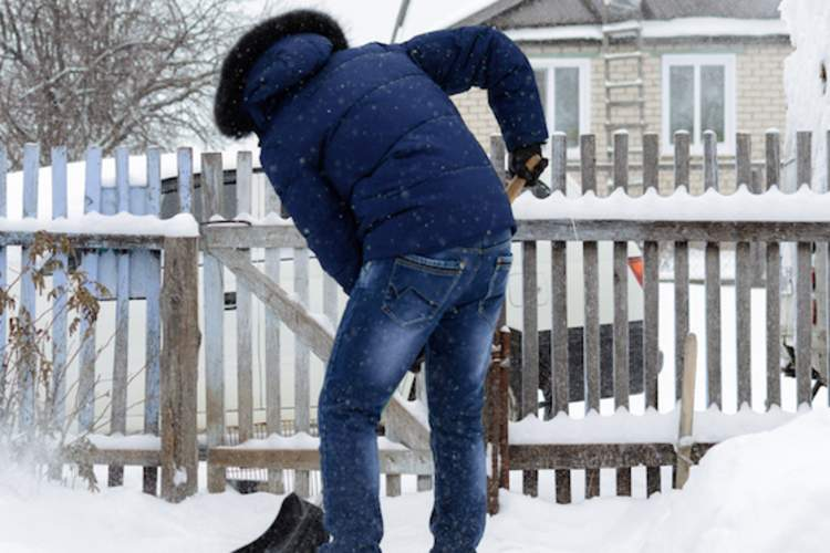 A man gets a back spasm while shoveling snow.