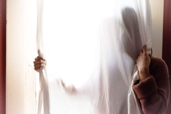 woman hiding behind curtain