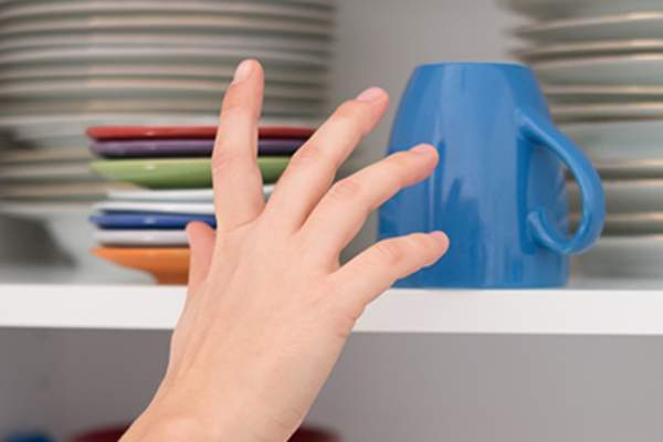 Hand reaching for a mug in a cabinet.